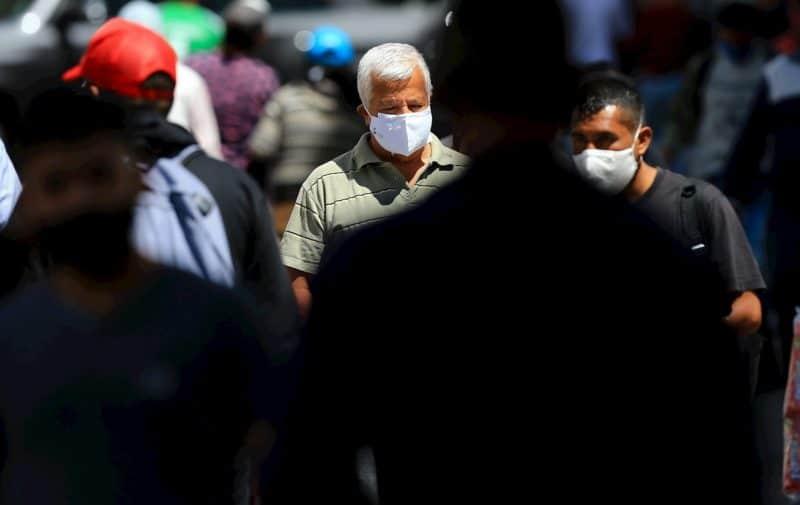 Ciudadanos ecuatorianos transitan con mascarillas hoy por las calles de Quito (Ecuador).